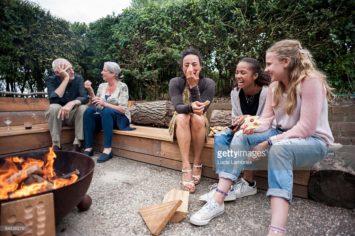 Familie zit buiten bij een vuurtje