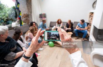Oudere vrouw maakt familiefoto met smartphone
