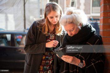 Oudere vrouw met smartphone krijgt hulp